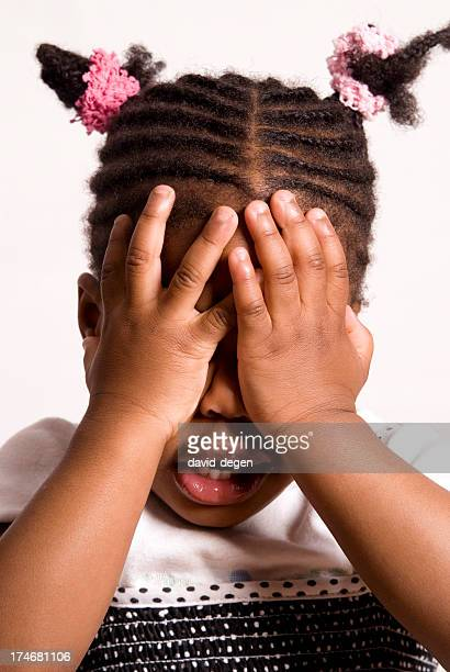 Black Little Girl With Hands In Front Of Her Face