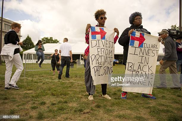 Black Lives Matter and 'Get Equal' protestors Angela Peoples and Rian Brown hold signs as Democratic presidential candidate aa Hillary Clinton speaks...