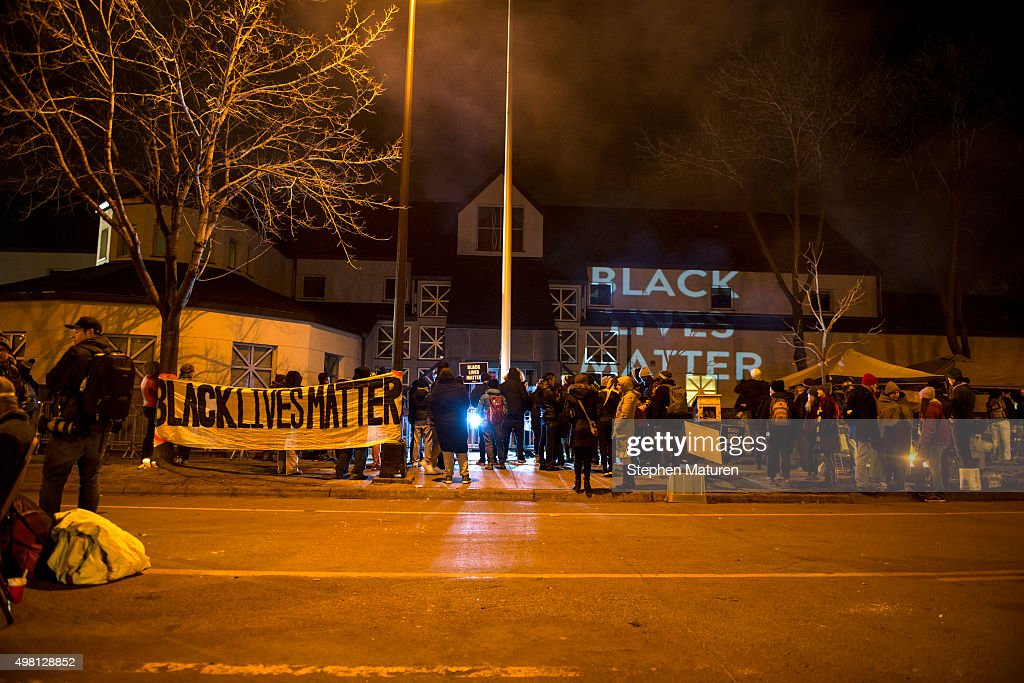 Black Lives Matter organizers project slides reading 'BLACK LIVES MATTER' on the walls outside the 4th Precinct police station November 20 2015 in...