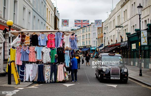 A black London taxi cab drives beneath a Union flag flying over stalls at Portobello Road Market in the Notting Hill district of west London on...