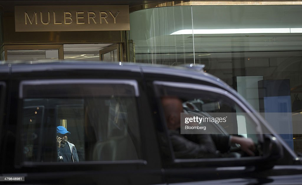 A black London taxi cab passes a Mulberry Group Plc luxury store on New Bond Street in London, U.K., on Thursday, March 20, 2014. Mulberry Group said Bruno Guillon will step down as chief executive officer after two years during which the British luxury handbag maker lost two-thirds of its market value. Photographer: Simon Dawson/Bloomberg via Getty Images