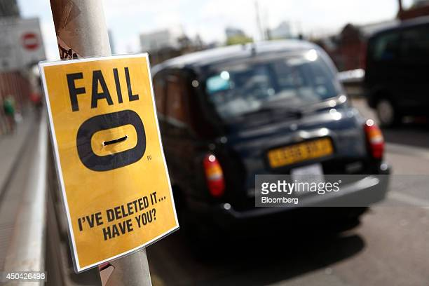 A black London taxi cab passes a poster protesting against the Hailo smartphone app outside Waterloo train station ahead of a protest against Uber...