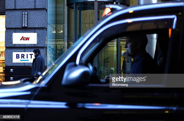 A black London taxi cab passes the entrance to the headquarters of Brit Plc a specialty insurer and reinsurer in London UK on Tuesday Feb 17 2015...