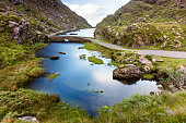 The River Loe and narrow mountain pass road wind through the steep valley of the Gap of Dunloe, nestled in the Macgillycuddy's Reeks mountains of Ireland's County Kerry.