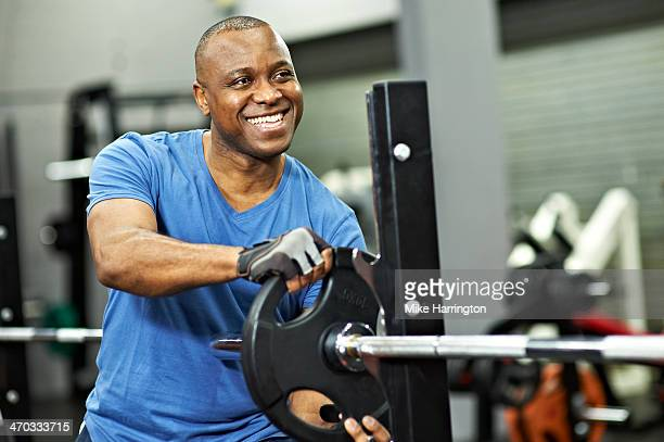 Black Male adding weight to gym equipment