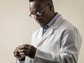 Black male in lab coat examining object