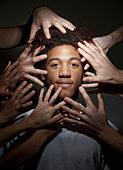 Black male surrounded by hands