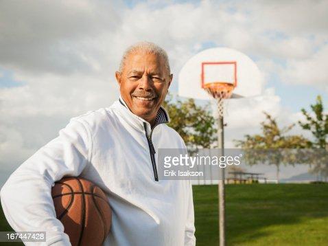Black man carrying basketball : Stock Photo