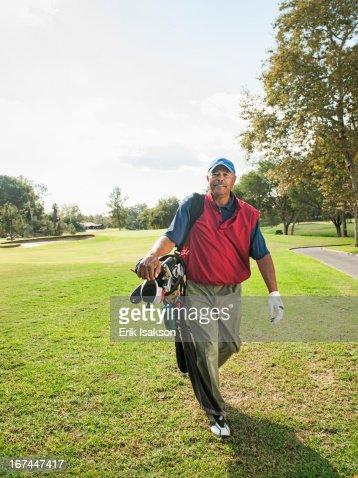 Black man carrying golf clubs : Stock Photo
