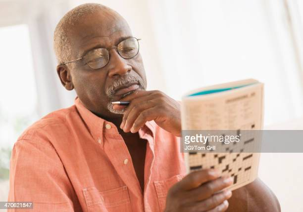 Black man doing crossword puzzle