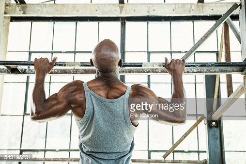 Black man doing pull-ups in warehouse : Stock Photo