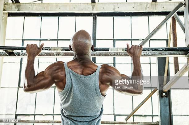 Black man doing pull-ups in warehouse