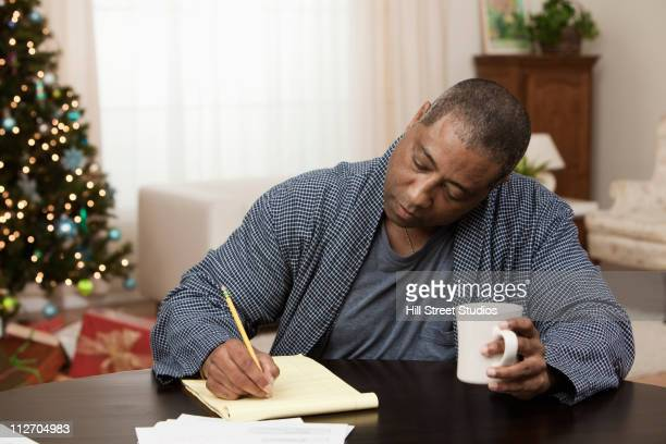 Black man drinking coffee and writing on notepad at Christmastime
