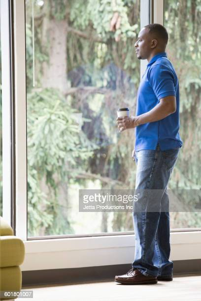 Black man drinking coffee at window