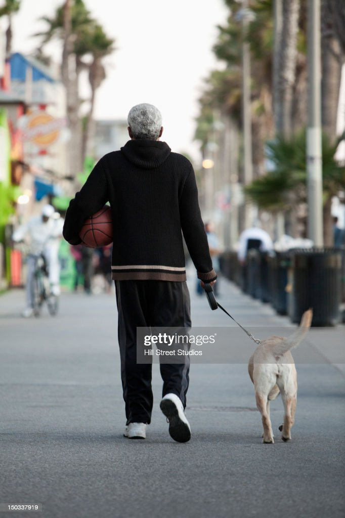 Black man holding basketball and walking dog : Stock Photo