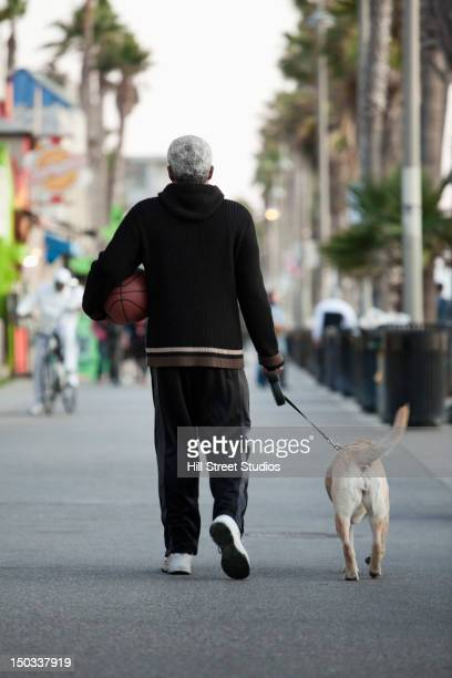 Black man holding basketball and walking dog