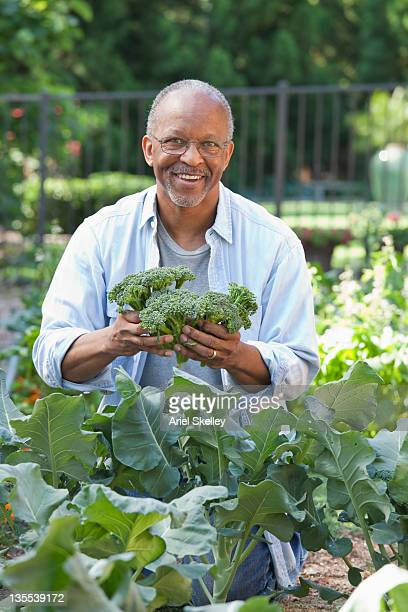 Black man holding broccoli in garden