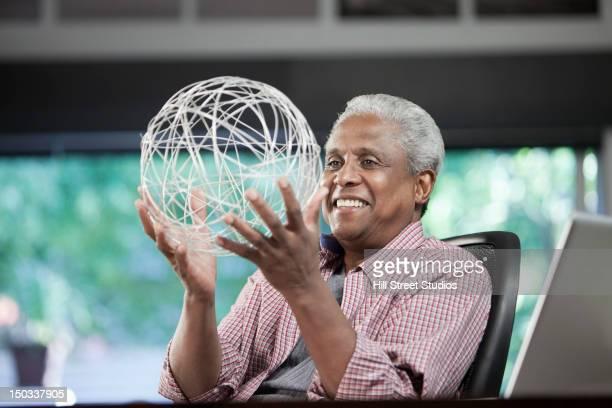 Black man holding string globe