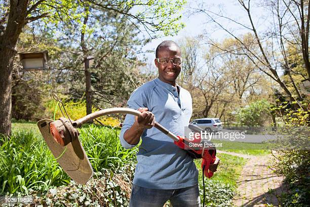 Black man holding weed trimmer