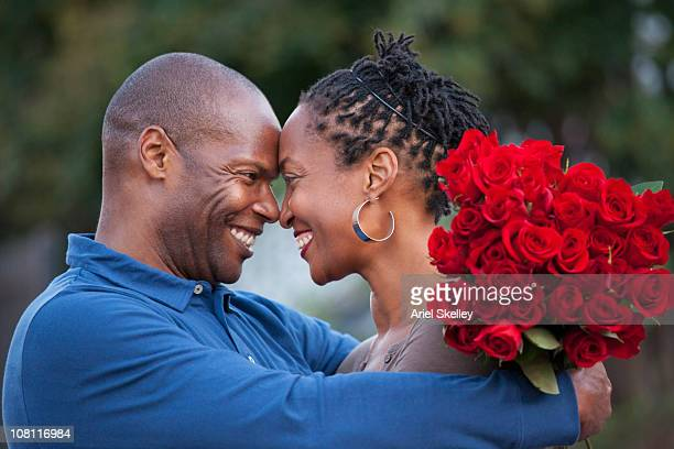 Black man hugging wife and giving her red roses