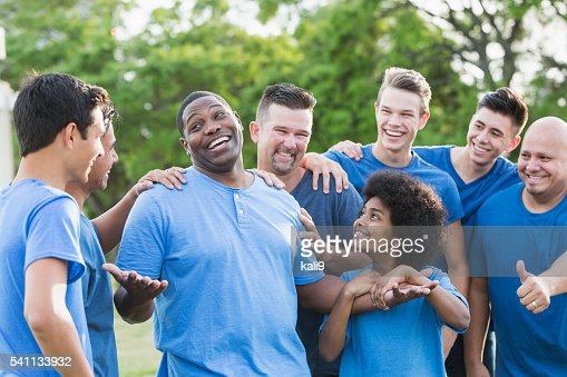 Black man in group getting pat on back