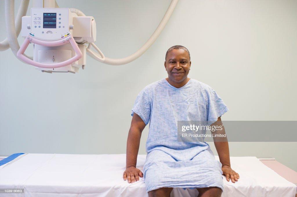 Black man in hospital gown sitting on gurney