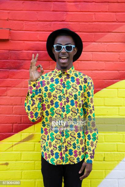 Black man in sunglasses making okay sign near colorful wall