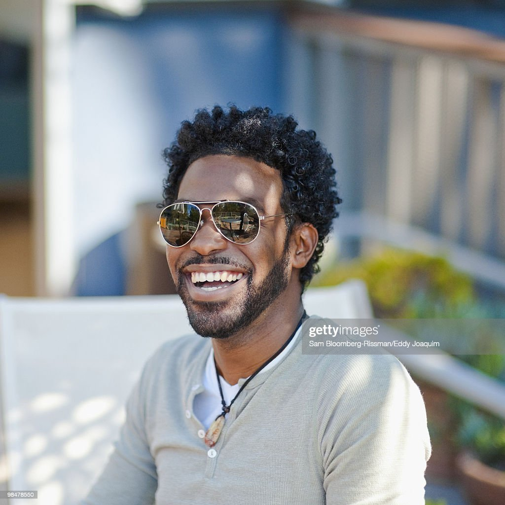 Black man in sunglasses smiling : Stock Photo