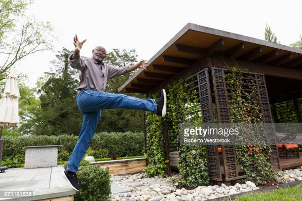 Black man jumping mid-air from bench in garden