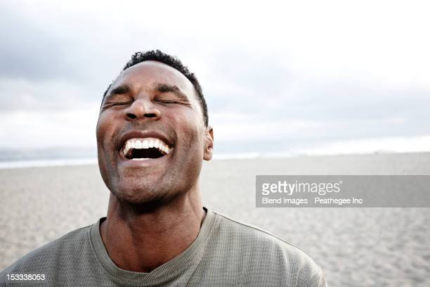 Black man laughing on beach