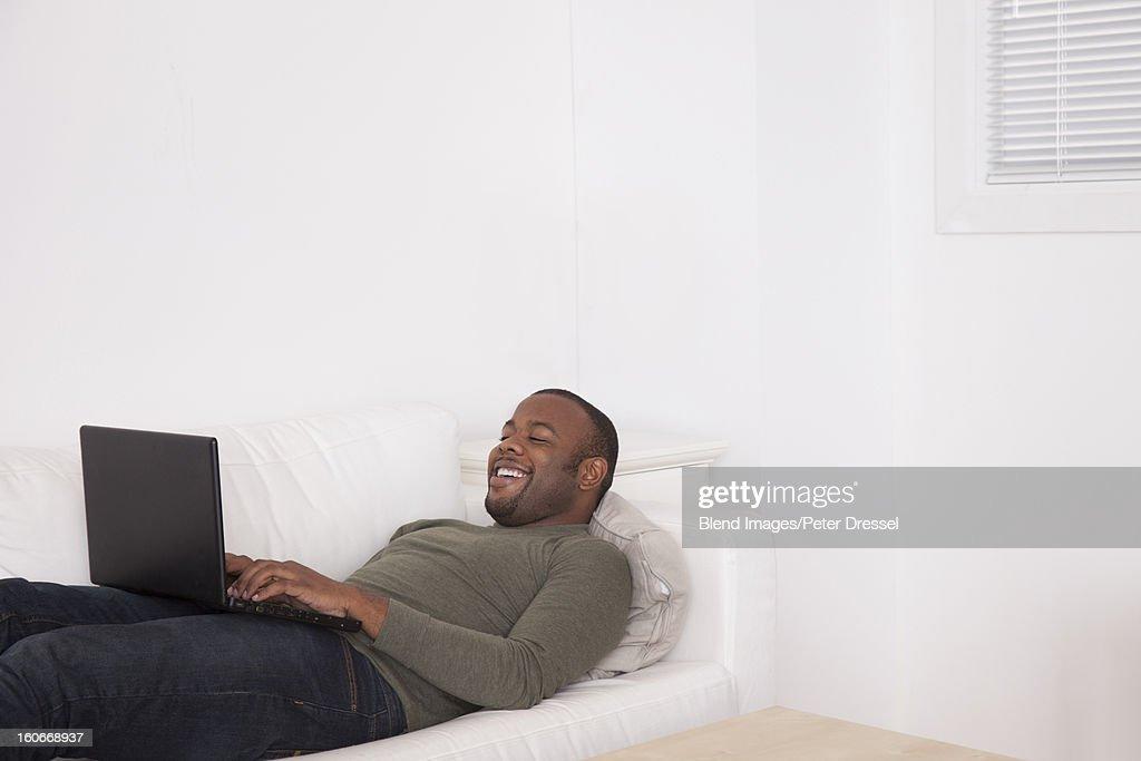 Black man laying on sofa using digital tablet : Stock Photo