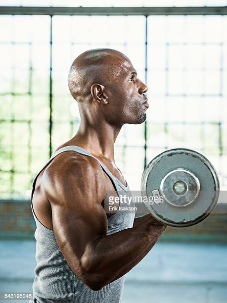 Black man lifting weights in warehouse