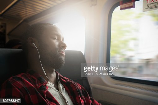 Black man listening to earbuds on bus