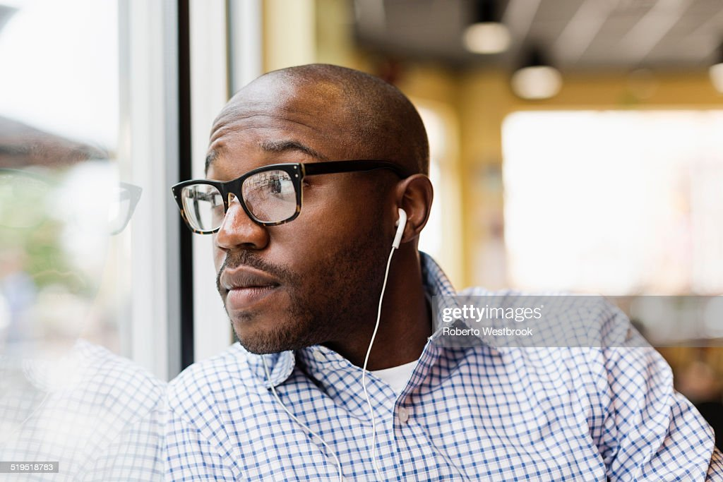 Black man listening to earphones in coffee shop