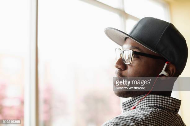 Black man listening to headphones indoors