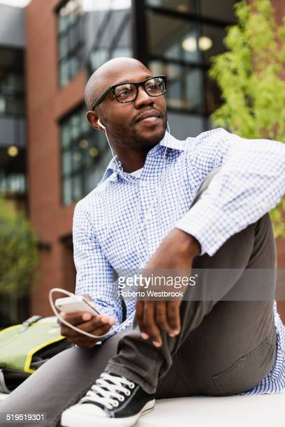 Black man listening to mp3 player in city