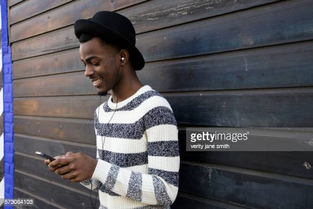Black man listening to mp3 player near wooden wall
