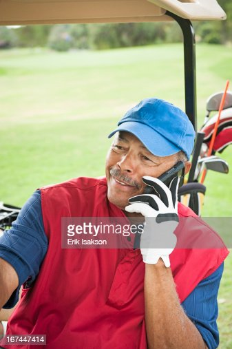 Black man on cell phone in golf cart : Stock Photo