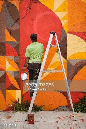 Black man painting wall