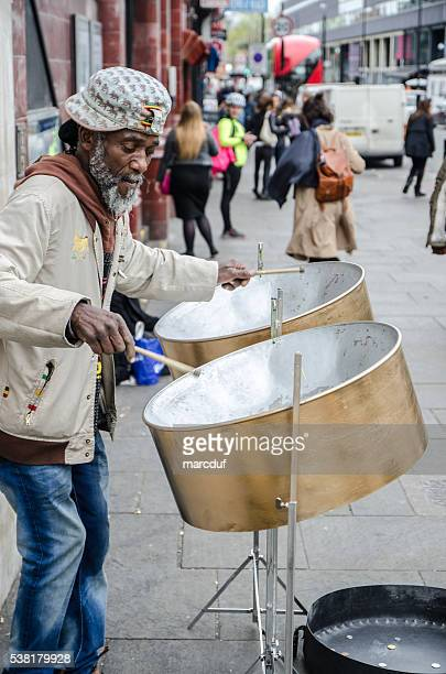 Hombre negro jugando Jamaiquino de los tambores de acero en la calle