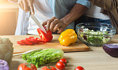 Black man cutting vegetables for healthy vegetarian salad in kitchen, closeup