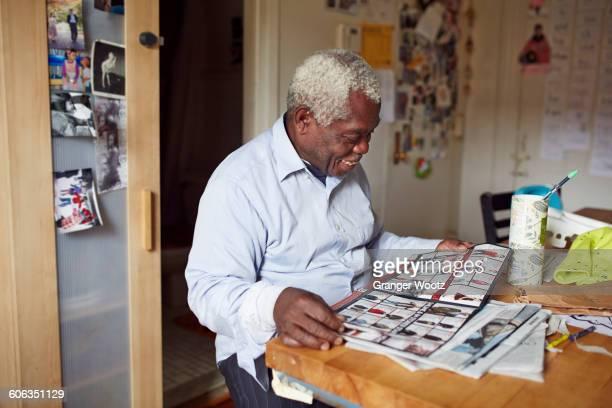 Black man reading magazine at table