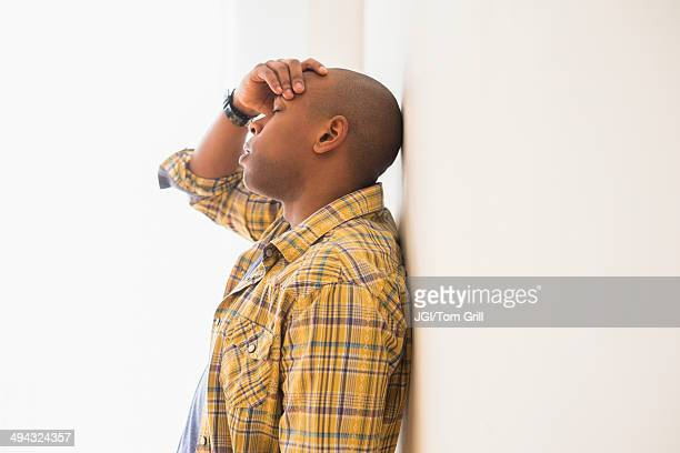 Black man rubbing his forehead