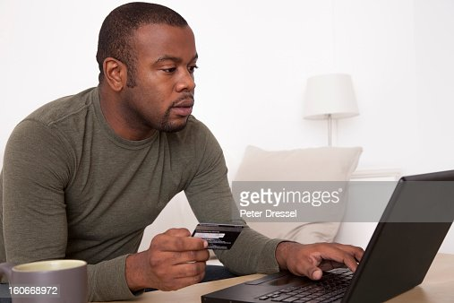 Black man shopping online with credit card : Stock Photo