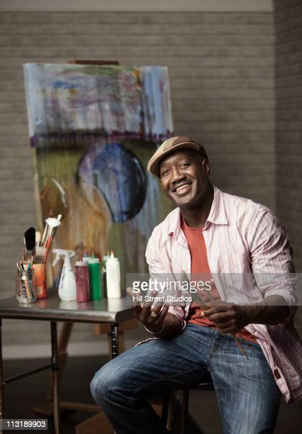 Black man sitting in artist's studio