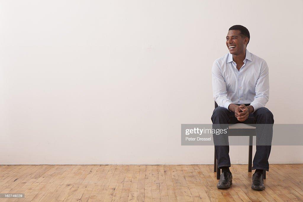 Black man sitting in chair