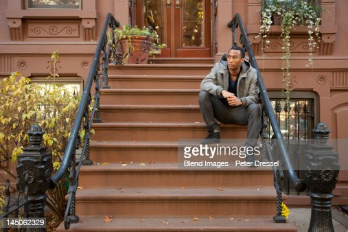 Black man sitting on front stoop