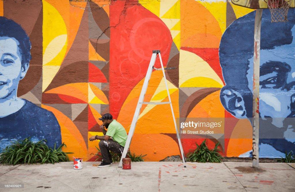Black man sitting on ladder by mural