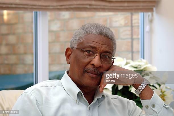 Black man sitting pensively in room