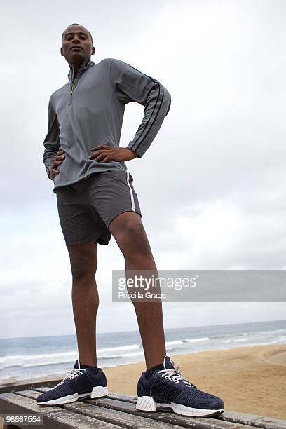 Black man standing on bench at beach